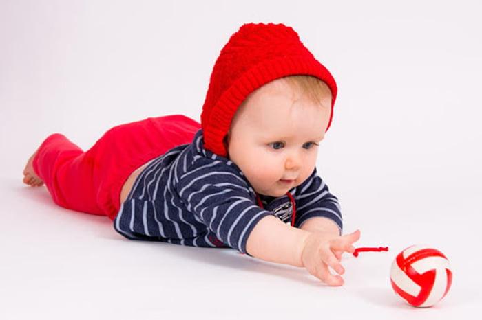 Малыш тянется к мячику