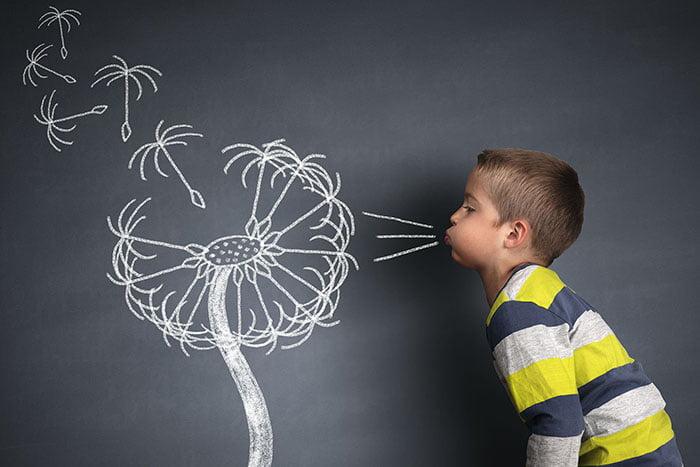 Ребенок дует на нарисованный одуванчик