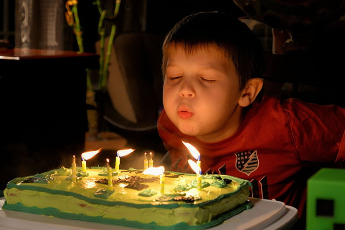 Ребенок задувает свечи на торте