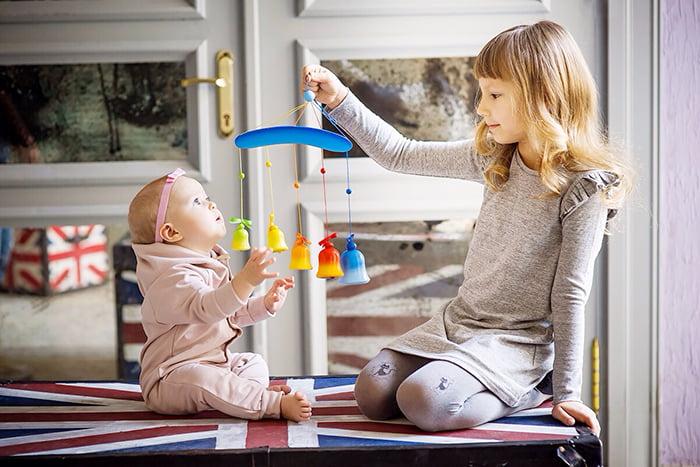Девочка играет с младшей сестричкой
