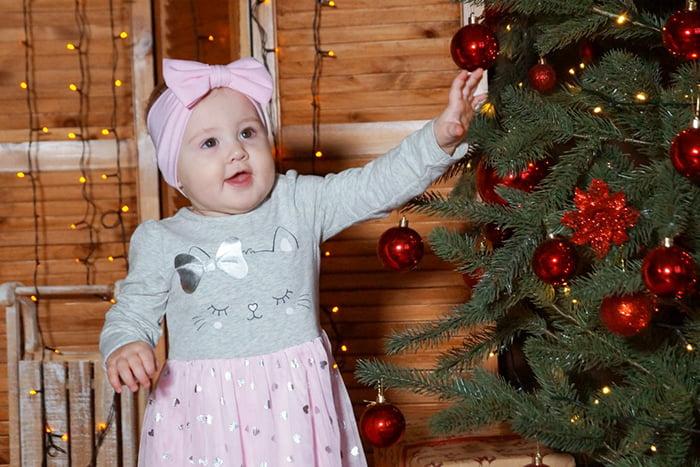 Годовалая девочка возле новогодней елки