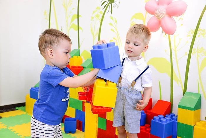 Двухлетние дети играют с большим конструктором