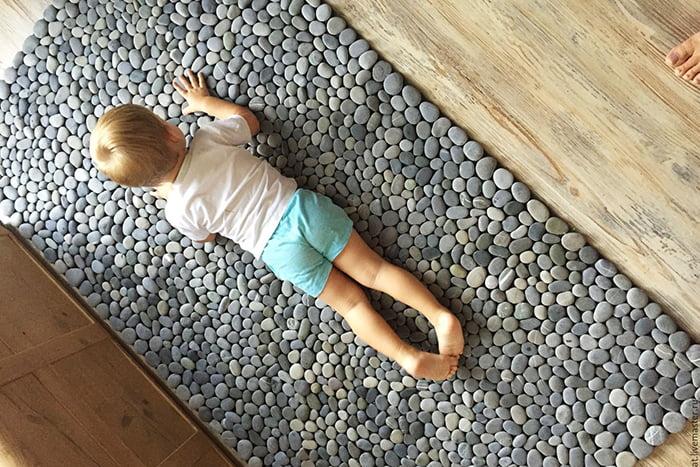 Ребенок лежит на коврике из гальки