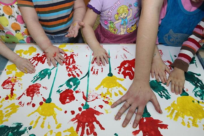 Дети рисуют цветы отпечатками ладошек