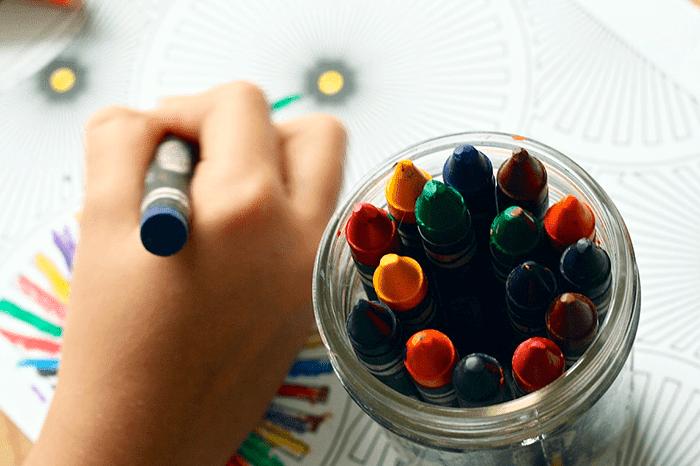 Ребенок раскрашивает рисунок восковыми мелками