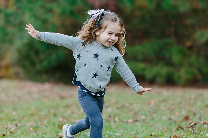 Девочка бежит, раскинув руки