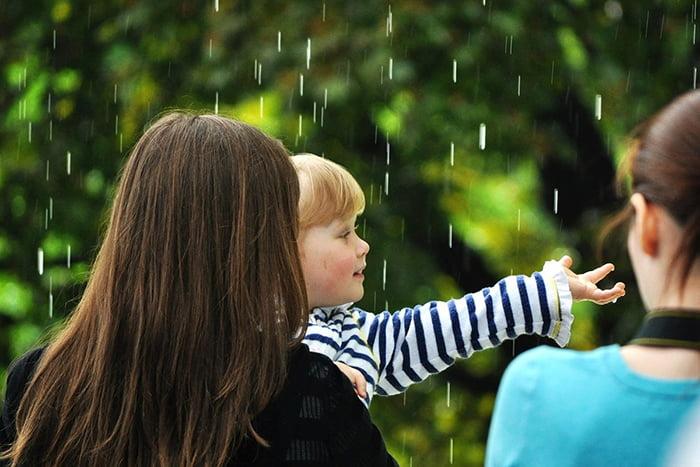 Ребенок под каплями летнего дождя