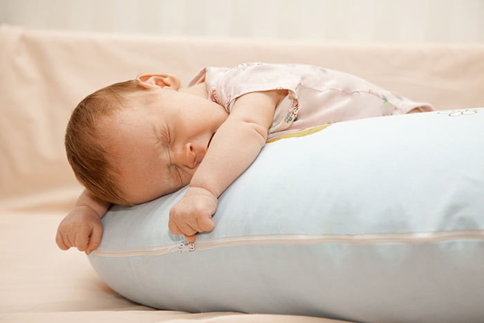 Малыш спит на большой подушке