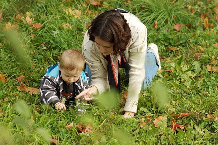 Мама с малышом на прогулке рассматривают растения