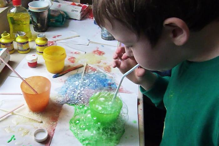 Ребенок рисует мыльными пузырями