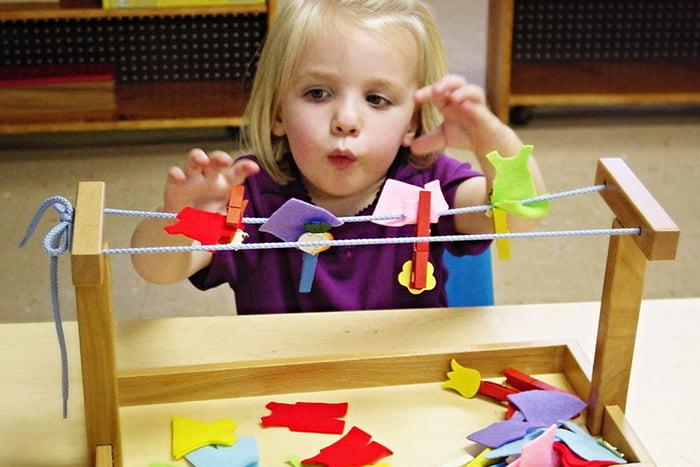 Двухлетняя девочка с развивающей игрушкой по Монтессори