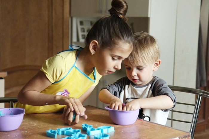Дети играют на кухне с тестом и формочками