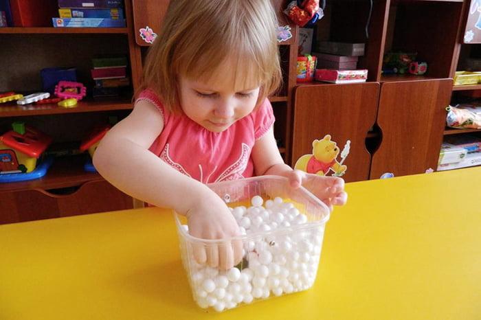Девочка играет с сенсорной коробочкой
