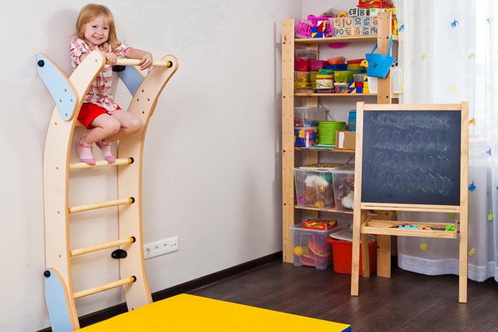 Четырехлетняя девочка на шведской стенке в детской