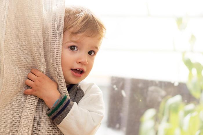 Ребенок прячется за шторой