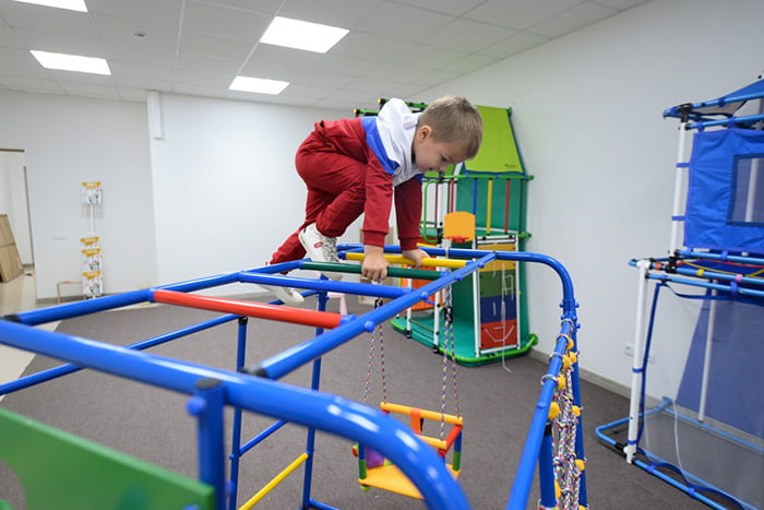 Ребенок на гимнастической лесенке в спортзале