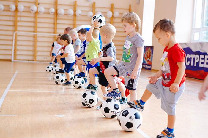 Дети с футбольными мячами на занятии