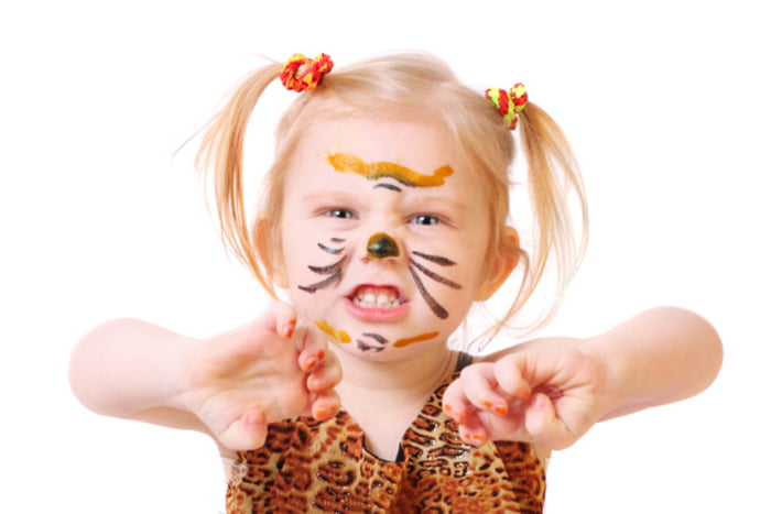 Маленькая девочка в костюме тигра рычит