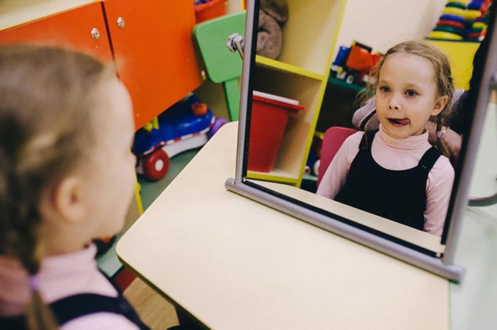 Девочка выполняет артикуляционные упражнения