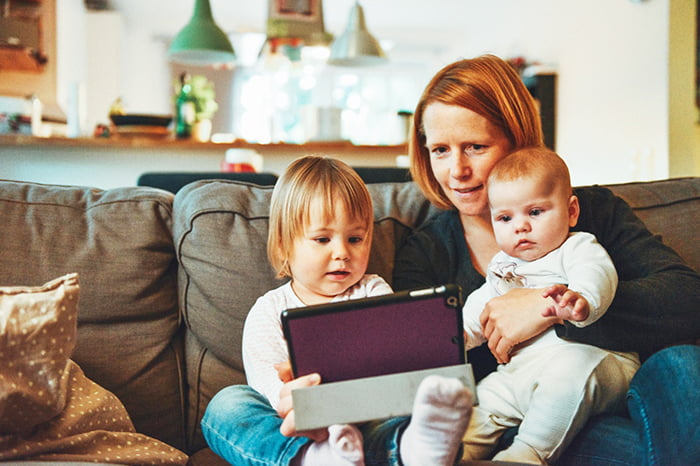 Мама показывает детям картинки на планшете
