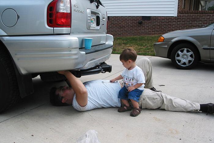 Малыш смотрит, как папа чинит машину