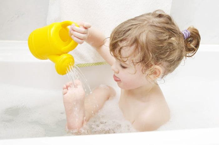 Маленькая девочка купается в ванне