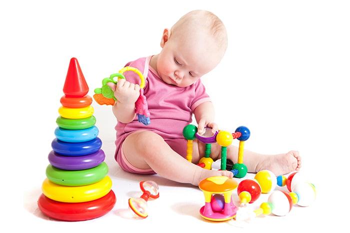 Годовалая девочка с пирамидкой и другими игрушками