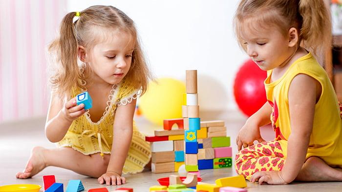 Девочки строят башню из кубиков и других фигур