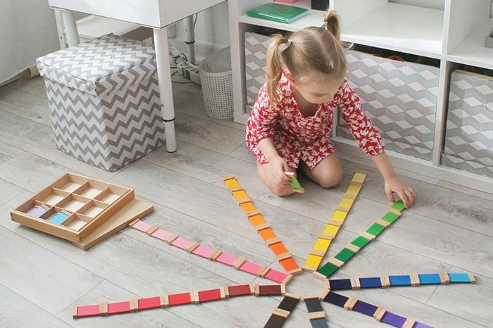 Девочка играет с разноцветными табличками Монтессори