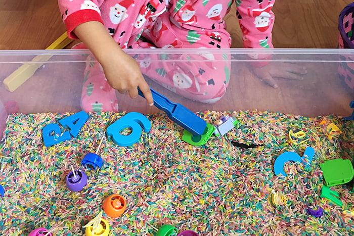 Ребенок играет с сенсорной коробкой, наполненной крупой и игрушками