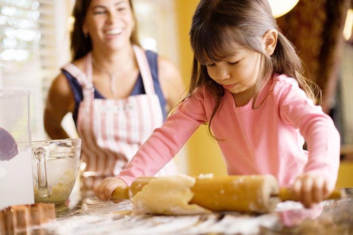 Девочка помогает маме на кухне