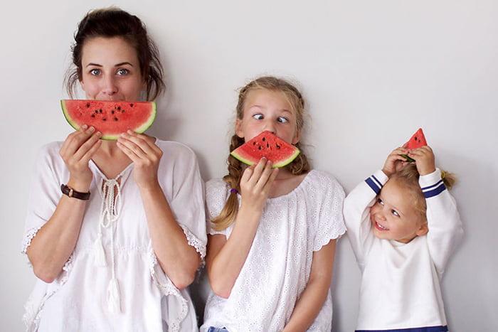 Мама и две дочки едят арбуз