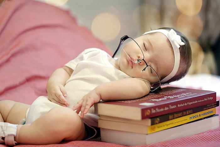 Трехмесячная девочка спит на стопке книг