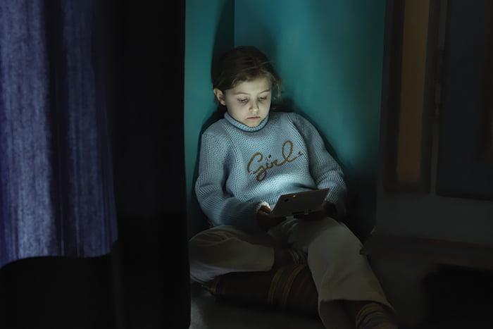 Девочка в углу с планшетом