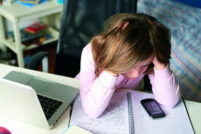 Девочка грустит рядом с компьютером и телефоном