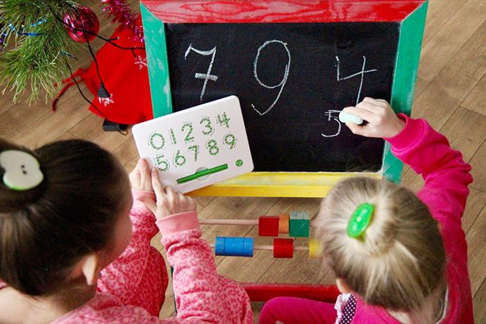 Девочки учатся писать цифры