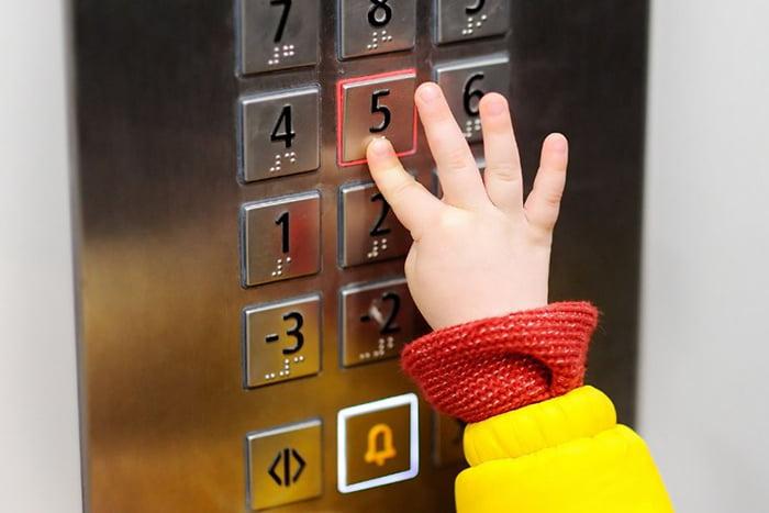 Ребенок нажимает кнопку в лифте