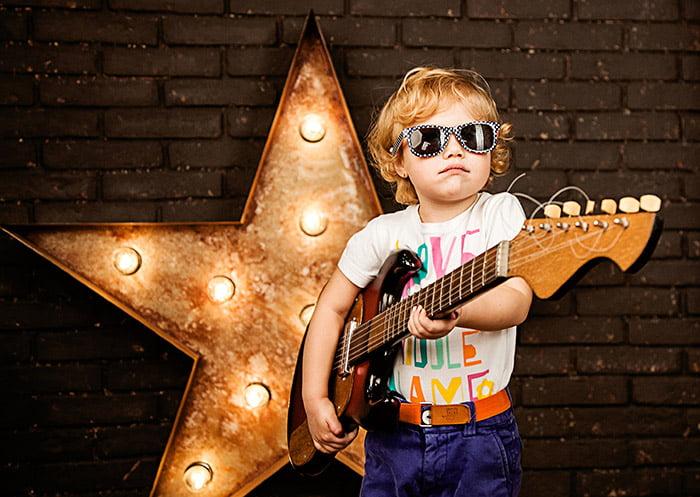 Ребенок с гитарой изображает рок-звезду