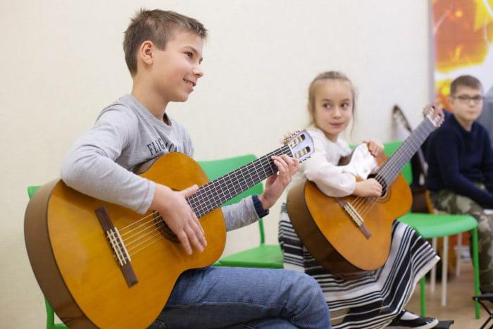 Дети учатся играть на гитаре