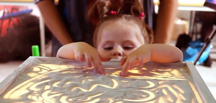 Маленькая девочка рисует на тонком слое песка