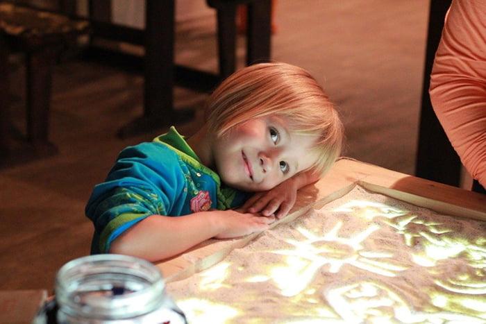 Девочка нарисовала солнышко на песке