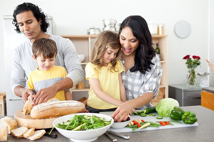 Родители с детьми режут овощи