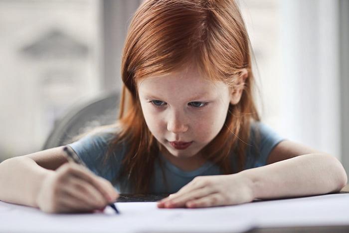 Девочка пишет на бумаге