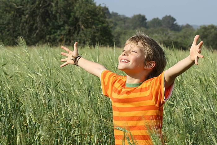 Мальчик радуется солнцу на природе