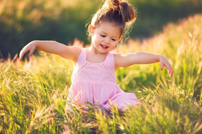 Маленькая девочка танцует в поле