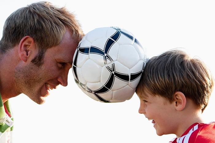 Папа с сыном играют с футбольным мячом