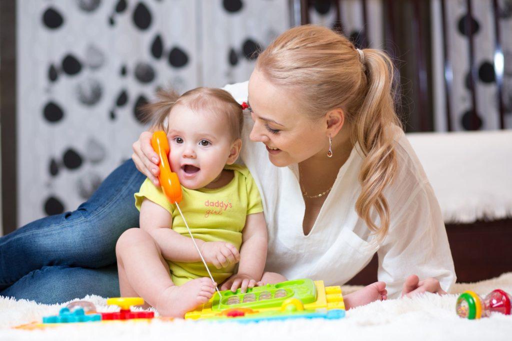 Мама с маленькой дочкой играют в телефон