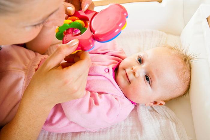 Мама показывает малышу погремушку
