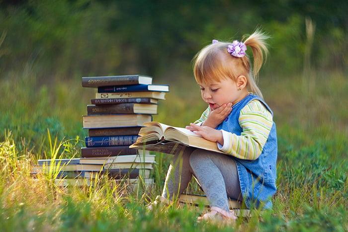 Девочка читает книгу на улице