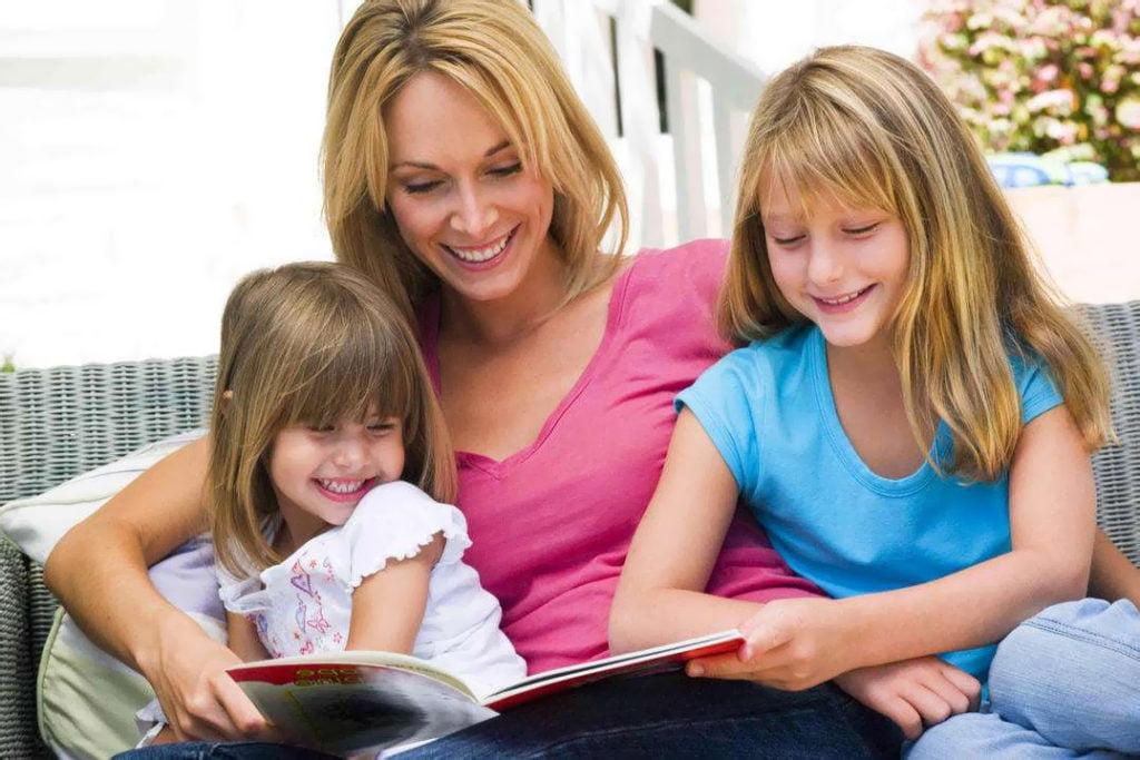 Мама с дочерьми читают книгу